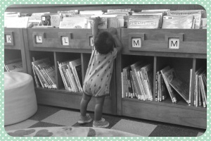 Munchkin prefers reading books, even though he suspects Mommy really brought him to the library in hopes that he would take a nap so that she could do some writing.